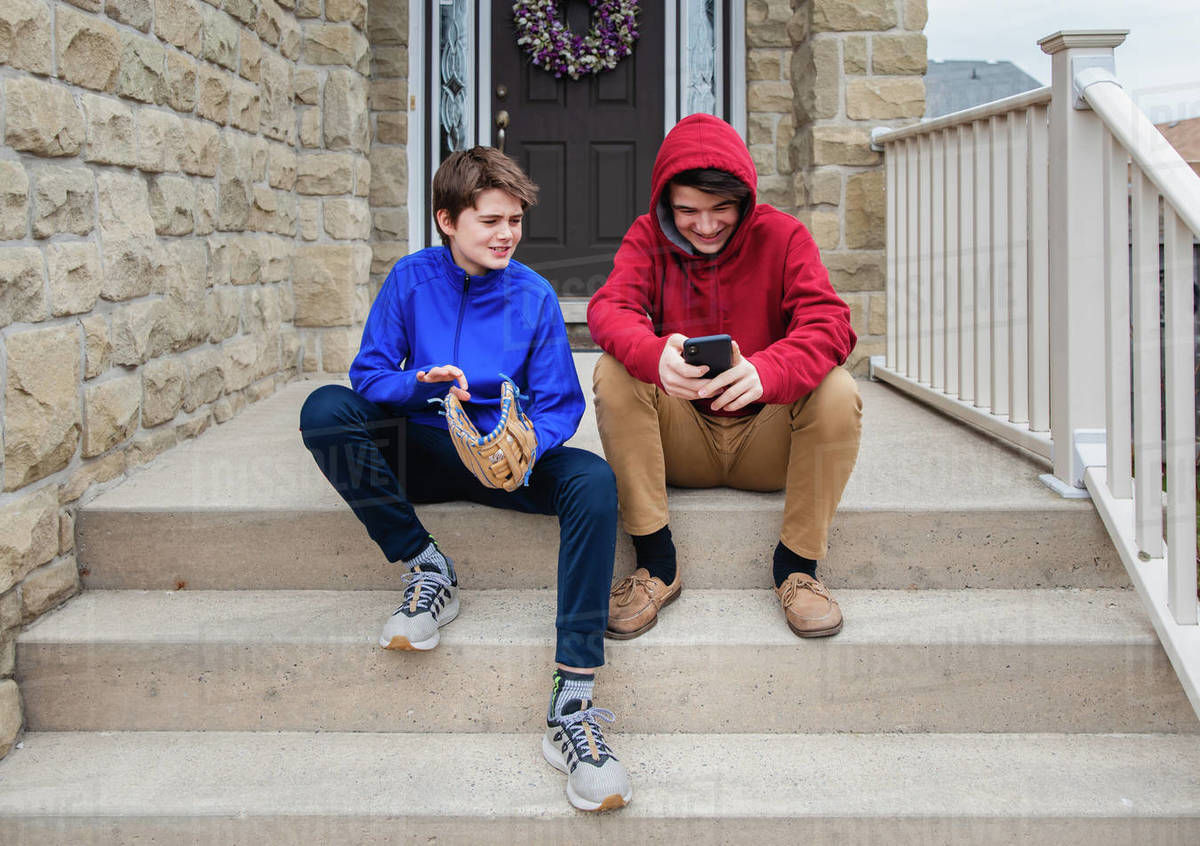 Two teenage boys sitting and talking on the front steps of a house. Royalty-free stock photo