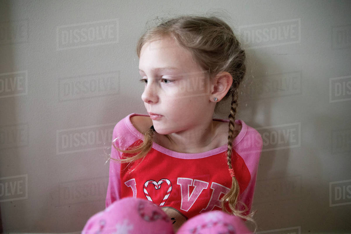 Blonde Girl in French Braids in Pajamas Looks Sadly Off-Camera Royalty-free stock photo