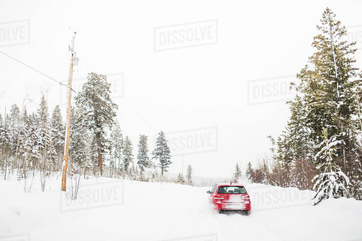 Rear view of red hatchback car driving on snow covered road. Royalty-free stock photo