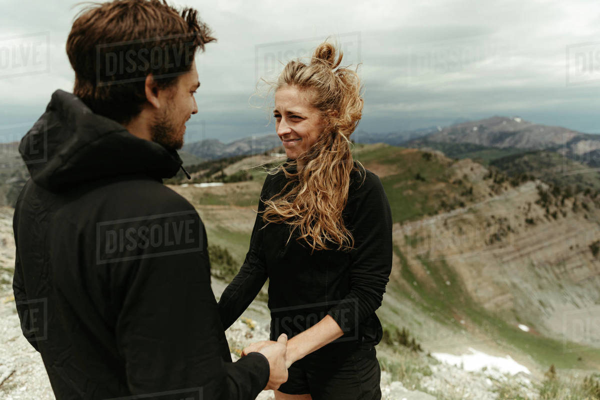 Woman awkward but happy, smiles during a surprise mountain engagement Royalty-free stock photo
