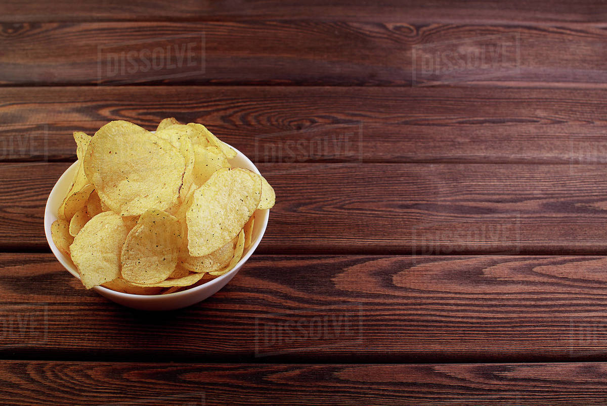 Cheese and chive potato crisp snack in brown bowl on wooden background Royalty-free stock photo