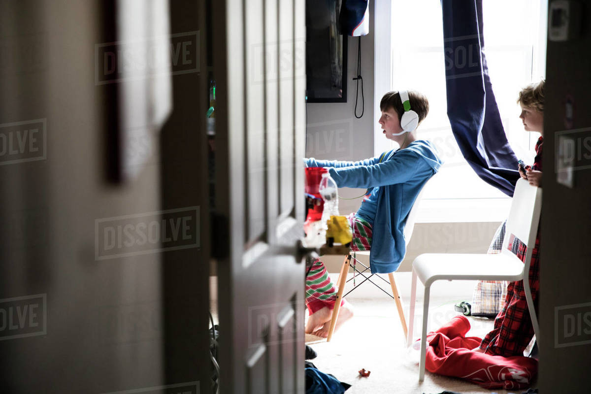 Little Brother Watches Teen Brother Play Video Games, Through Doorway Royalty-free stock photo