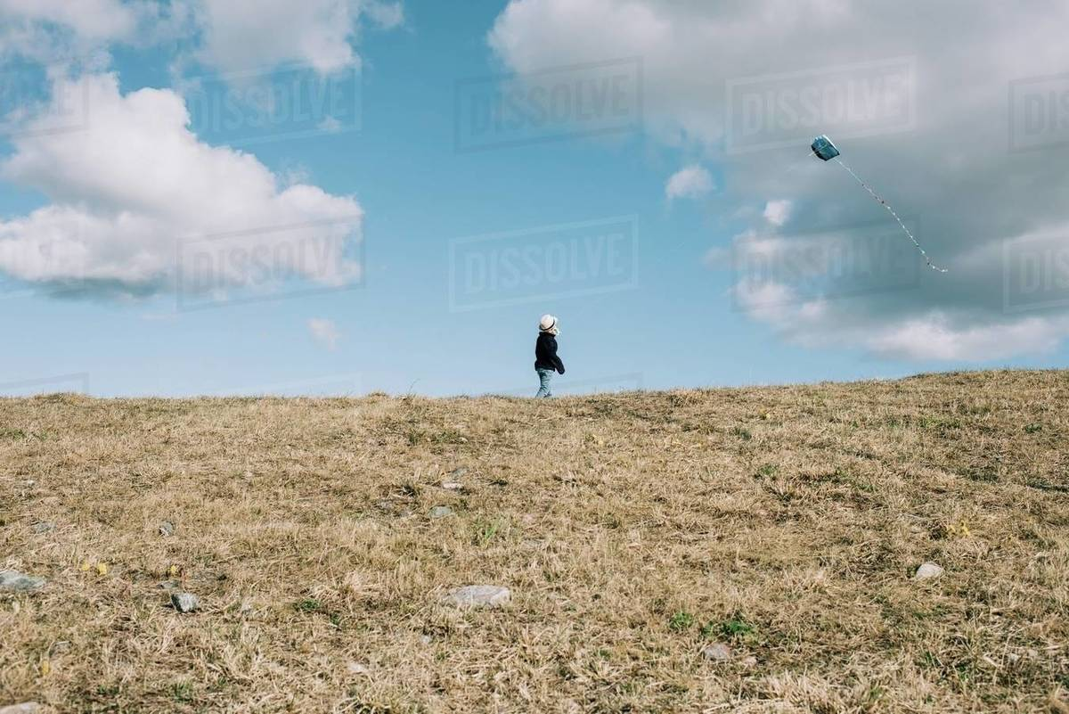 Young boy flying a kite on a hill on a sunny day Royalty-free stock photo