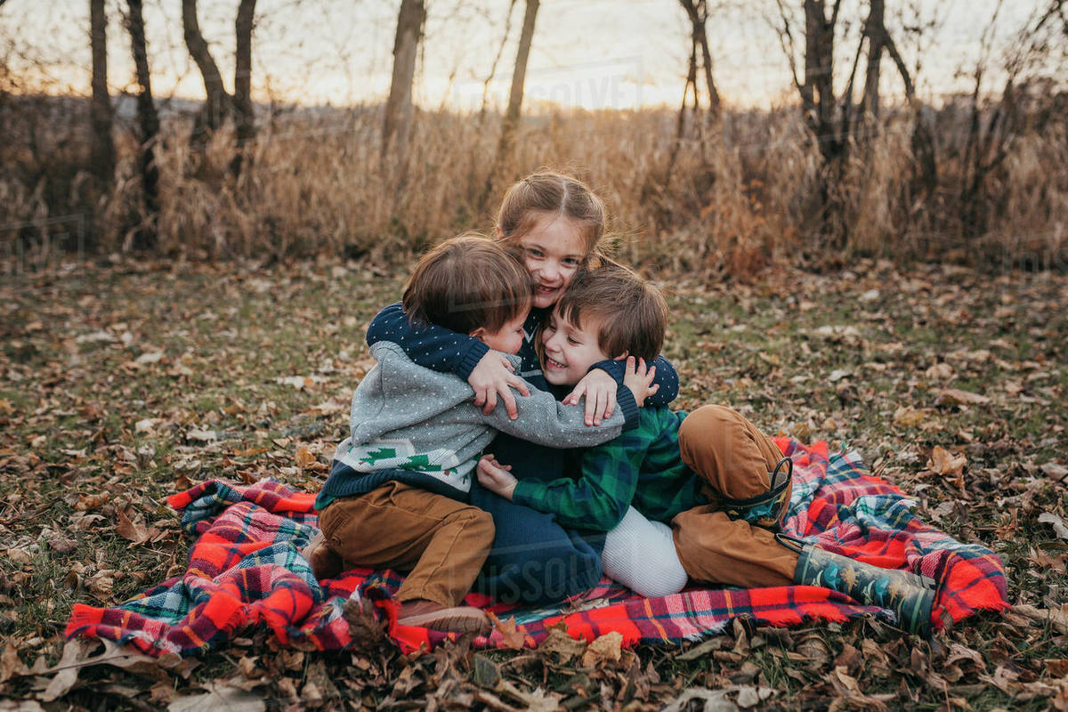 Three siblings sitting on red plaid blanket hugging at sunset Royalty-free stock photo