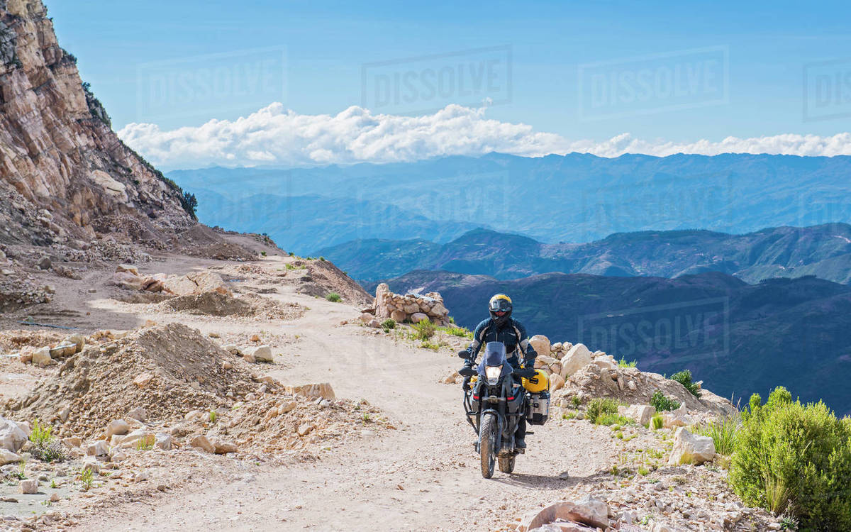 Man riding touring motorcycle on gravel road in Bolivia Royalty-free stock photo