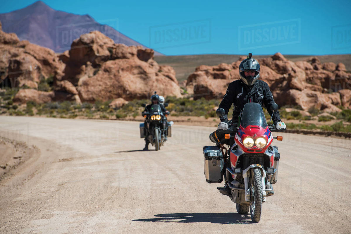 Two friends riding touring motorcycle's on dusty road in Bolivia Royalty-free stock photo