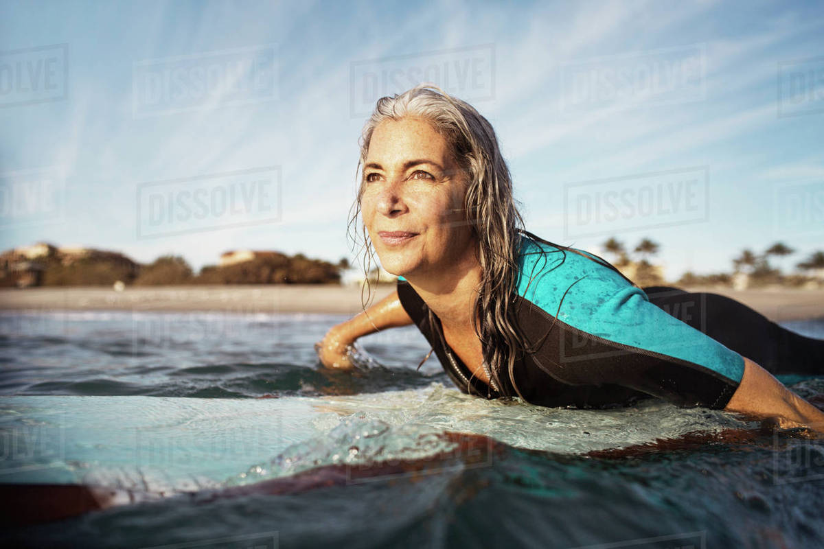 Mature woman looking away while surfing on sea Royalty-free stock photo