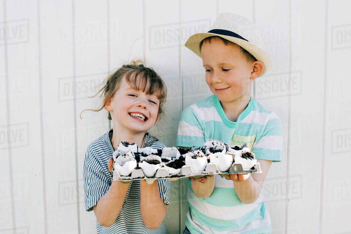 Siblings holding their planted seeds in egg shells up showing them off Royalty-free stock photo