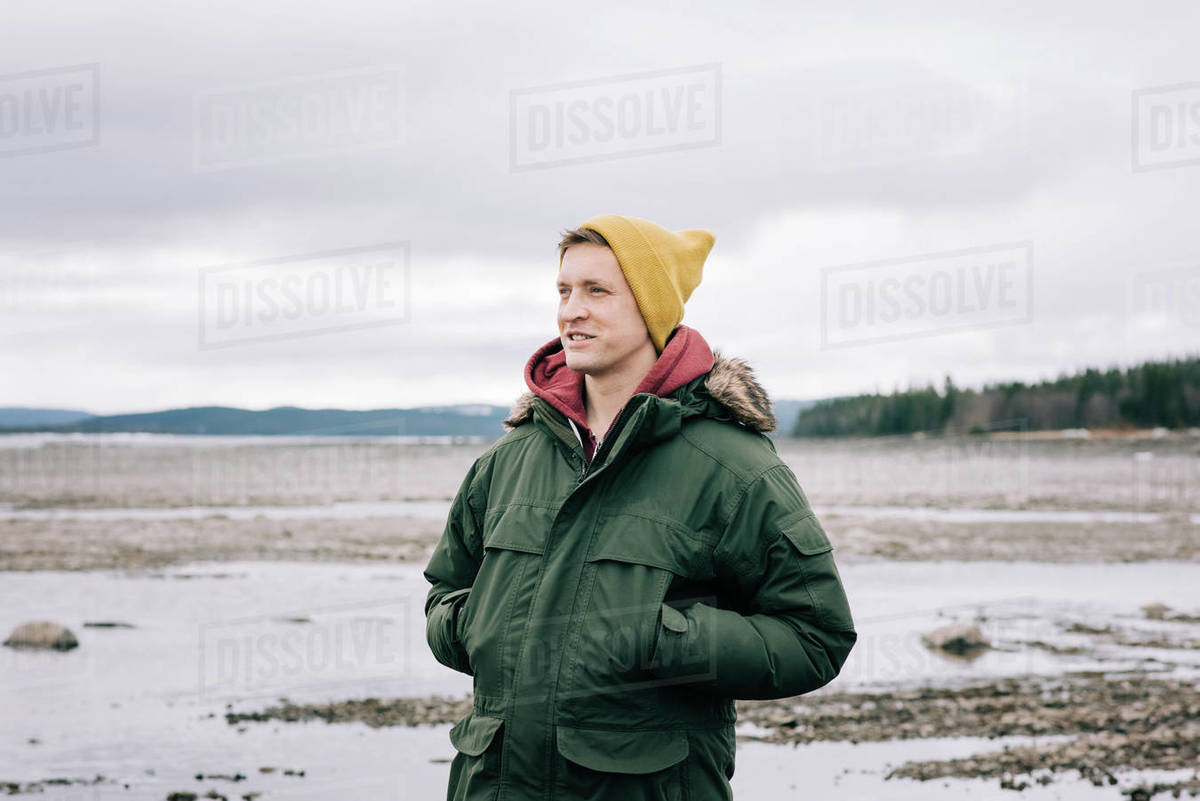 Portrait of a man smiling whilst standing alone in the great outdoors Royalty-free stock photo