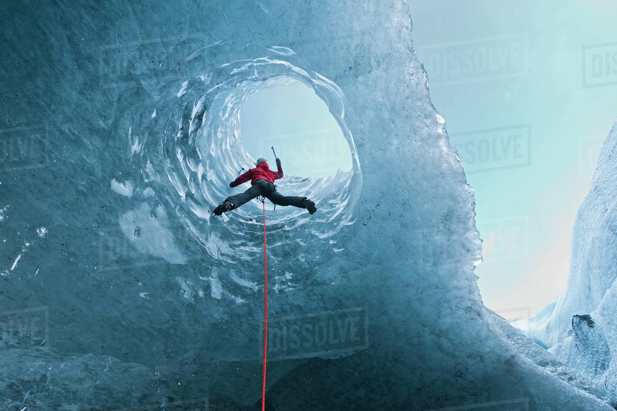 Woman climbing out of glacier cave / Sólheimajökull glacier in Iceland Royalty-free stock photo