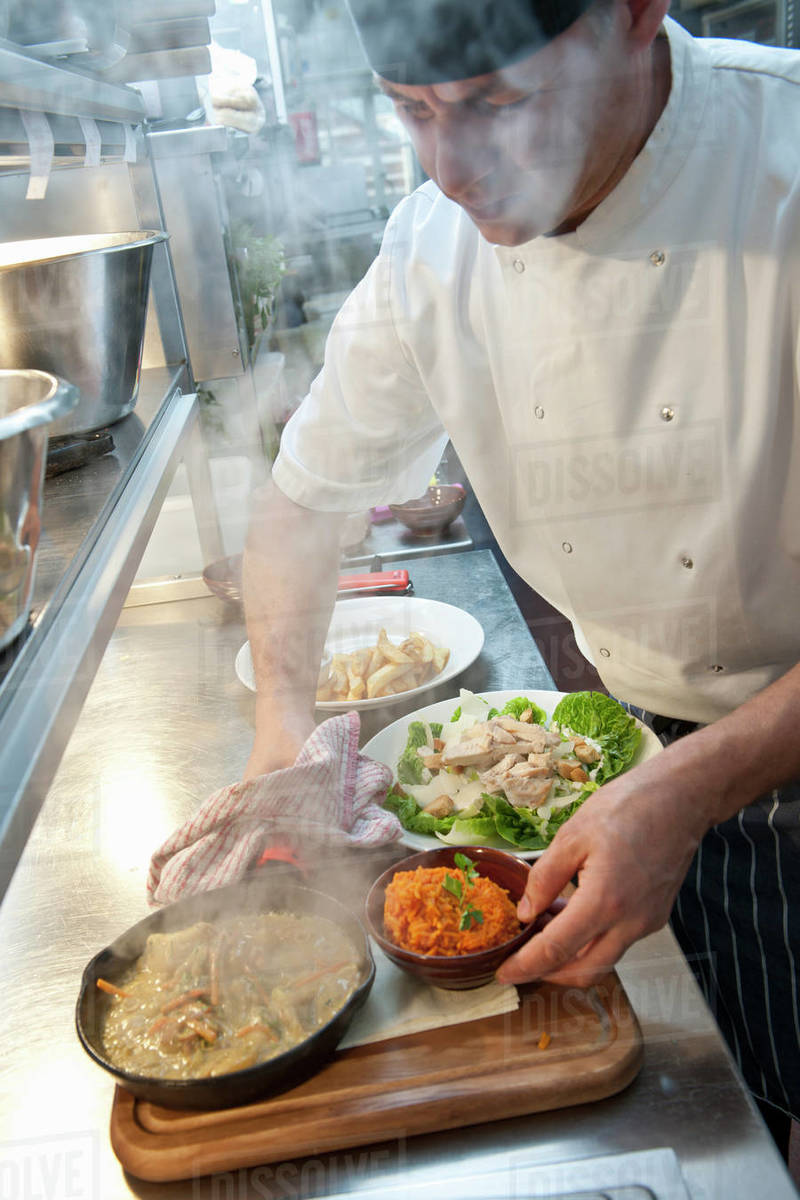 Chef preparing hot dish at commercial kitchen in British pub Royalty-free stock photo