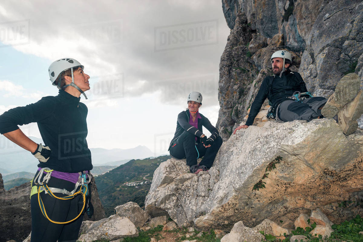 Concept: adventure. Three of climbers with helmet and harness. A man and two women. Resting relaxed sitting on a rock. Via ferrata in the mountains. Royalty-free stock photo