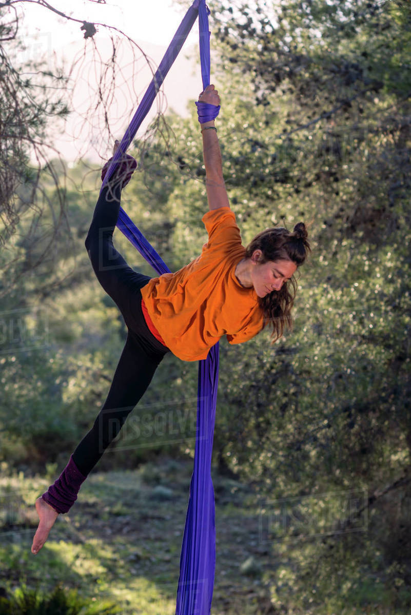 Young girl acrobat. Practicing aerial silks. Woman doing circus stunts with clothes in the forest. Figured head position. Royalty-free stock photo