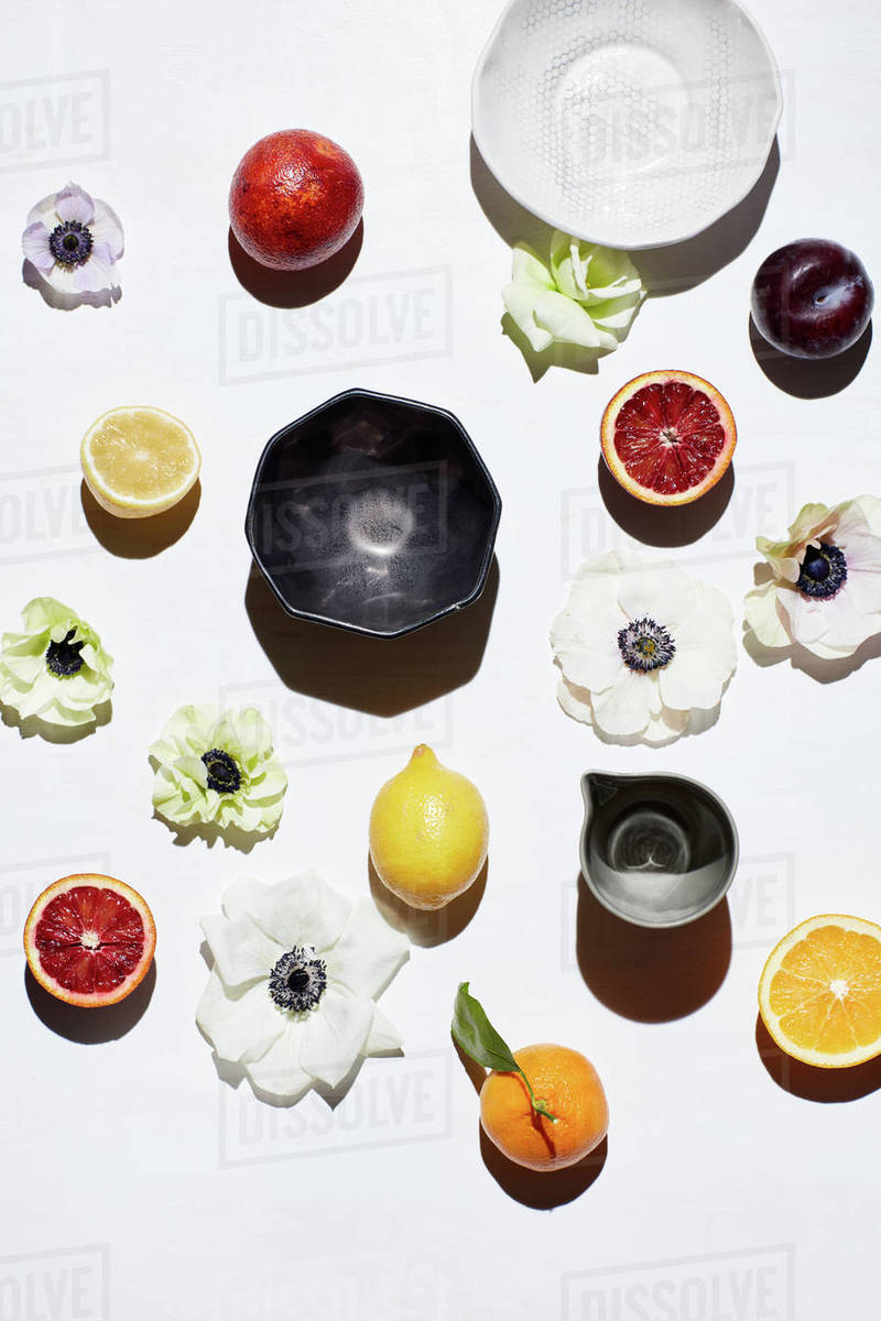 Still life with ceramic bowls, fruits and flower pedals Royalty-free stock photo