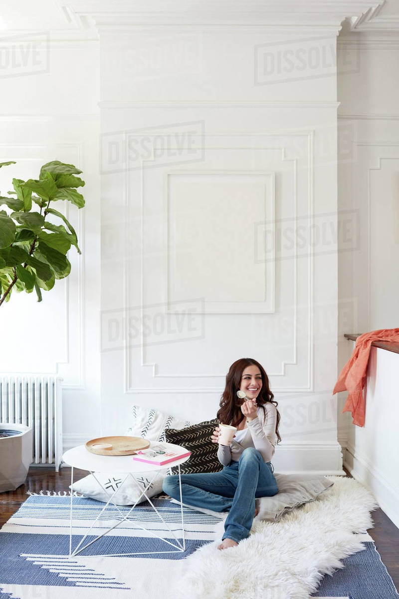 Woman eating ice cream on floor of living room Royalty-free stock photo