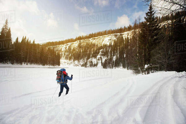 Rear view of hiker walking on snowcapped landscape Royalty-free stock photo