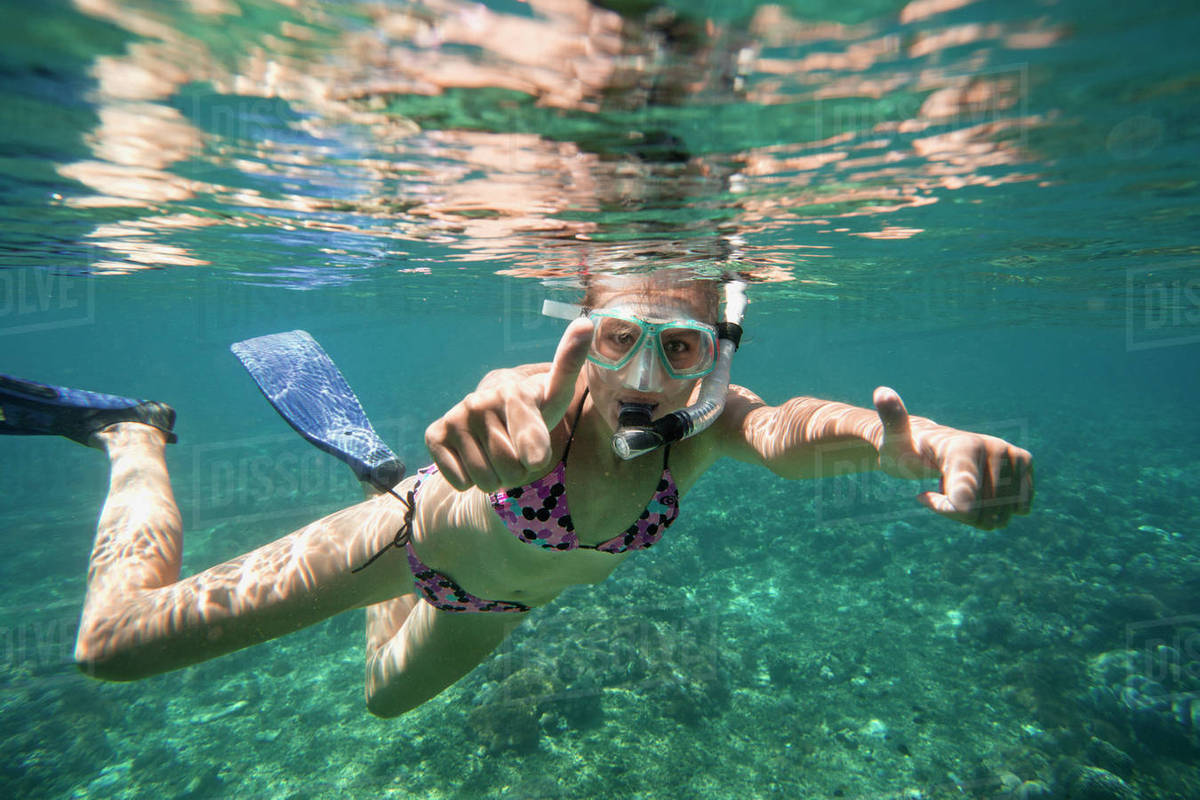 Portrait of successful woman showing thumbs up while snorkeling in sea Royalty-free stock photo