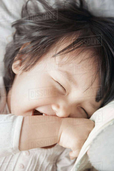 Close-up of happy playful girl lying on bed Royalty-free stock photo