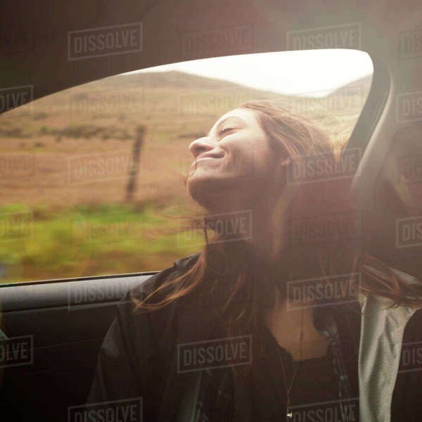 Carefree woman enjoying road trip in car at countryside Royalty-free stock photo