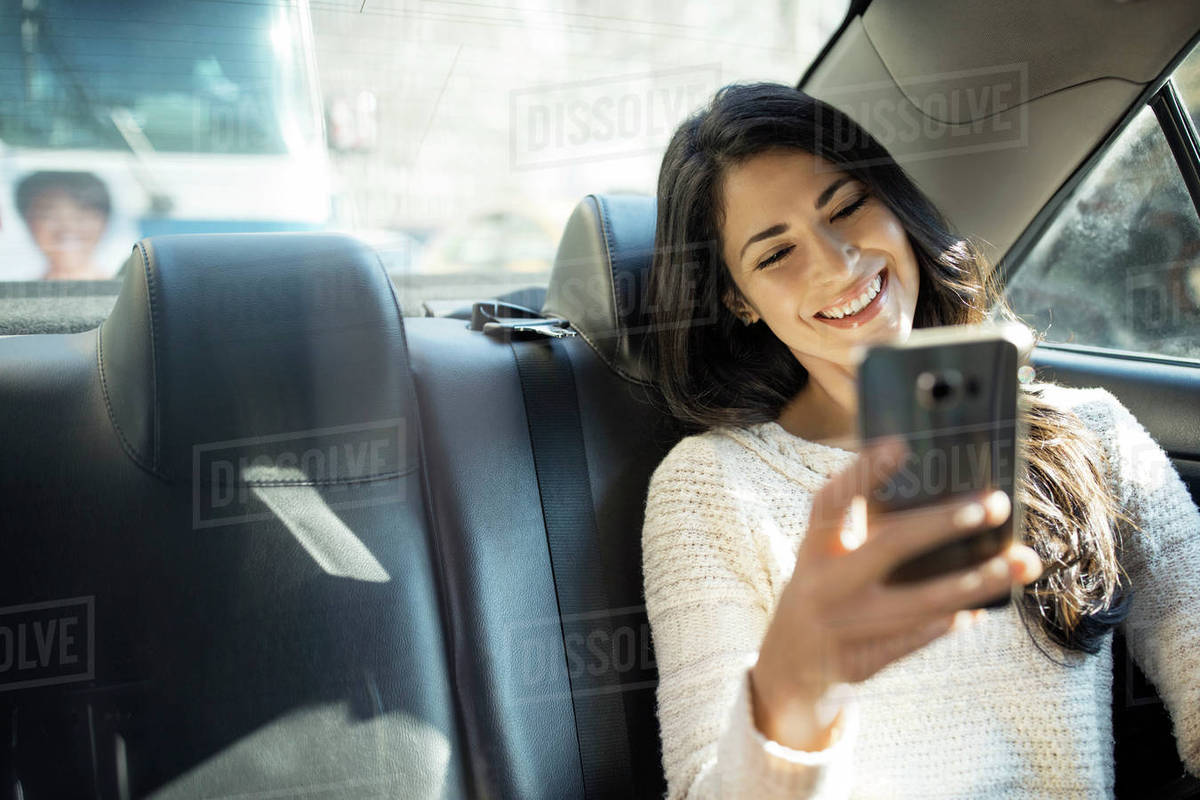 Happy young woman taking selfie through smart phone in taxi Royalty-free stock photo