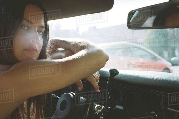 Portrait of young woman leaning on steering wheel in car Royalty-free stock photo