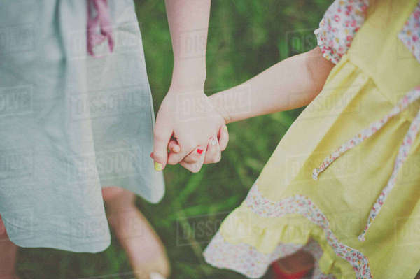 Midsection of girls holding hands on field Royalty-free stock photo