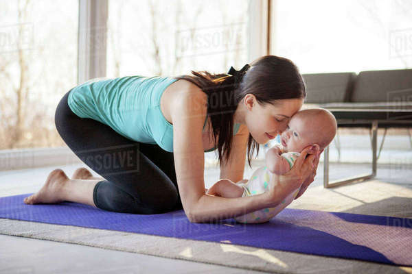 Loving mother holding baby girl while kneeling on exercise mat Royalty-free stock photo