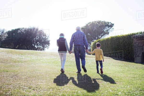 Rear view of grandparents walking with grandson on grassy field Royalty-free stock photo