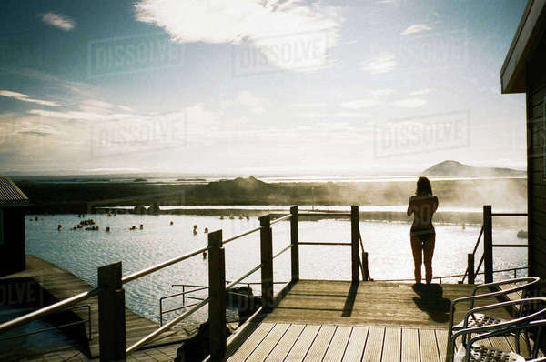 Rear view of woman standing on steps by lake against sky Royalty-free stock photo