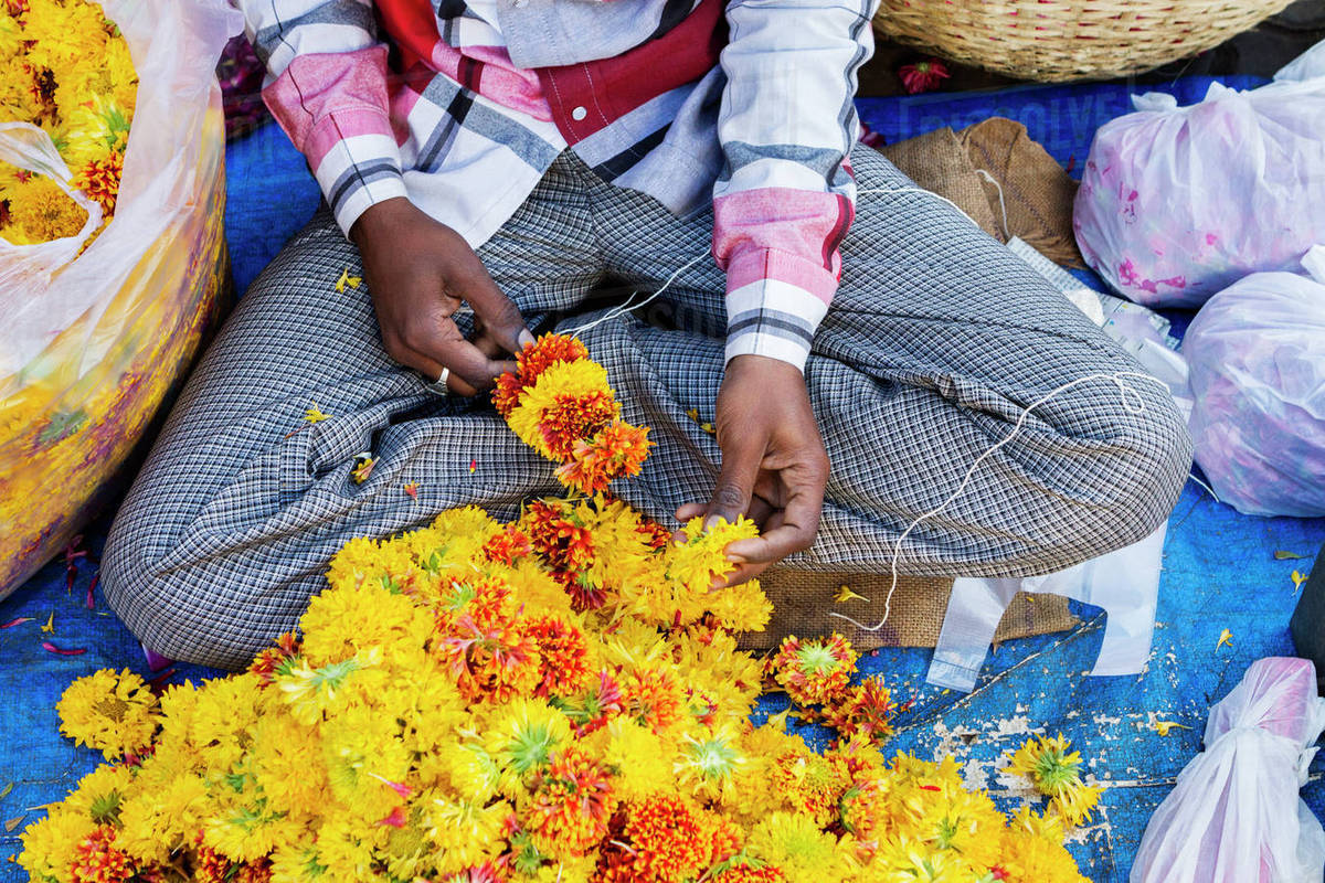 Overhead View Of Man Making Marigold Garland At Market Stall