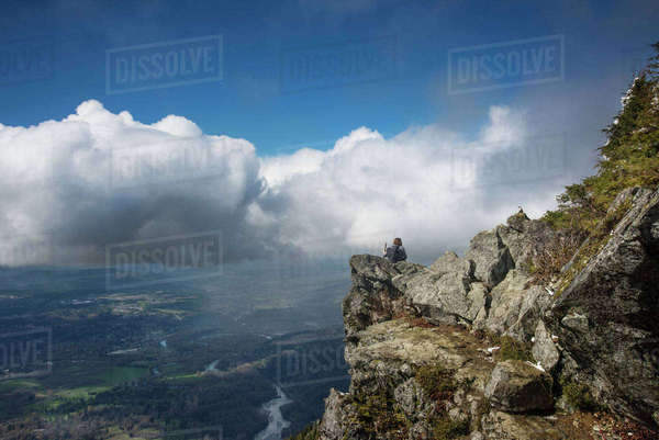 Man sitting on mountain top against cloudy sky Royalty-free stock photo