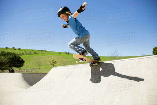 Low angle view of boy skateboarding on ramp against clear blue sky Royalty-free stock photo