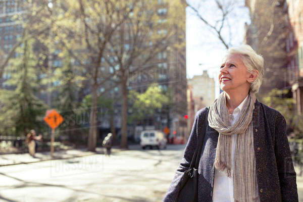 Thoughtful senior woman smiling on city street Royalty-free stock photo