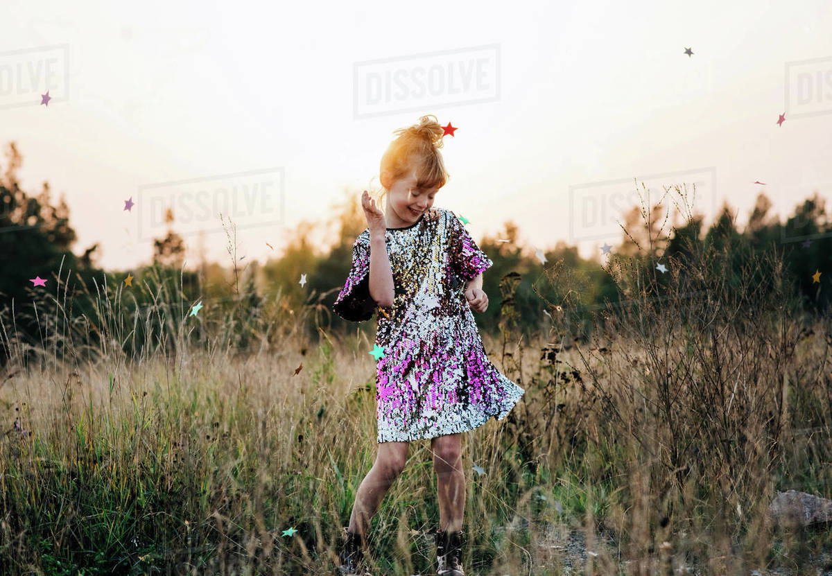 Girl happily dancing in a sparkly dress at sunset with star confetti Royalty-free stock photo