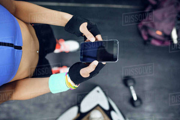 Overhead view of female athlete using smart phone at gym Royalty-free stock photo