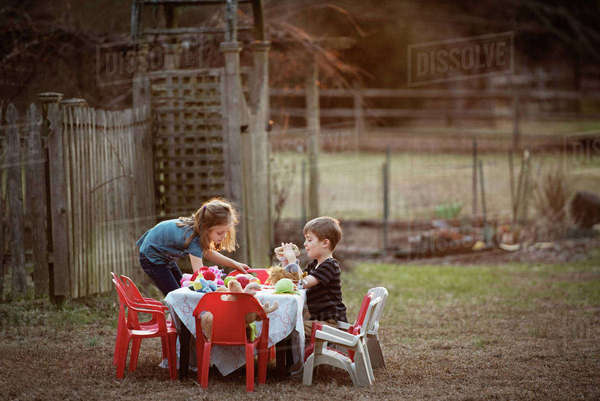 Side view of brother and sister having food at dining table in yard Royalty-free stock photo