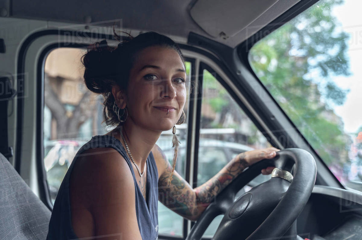 Young woman, with tattoos and piercings, driving a van, looks at the room with satisfied expression. Royalty-free stock photo