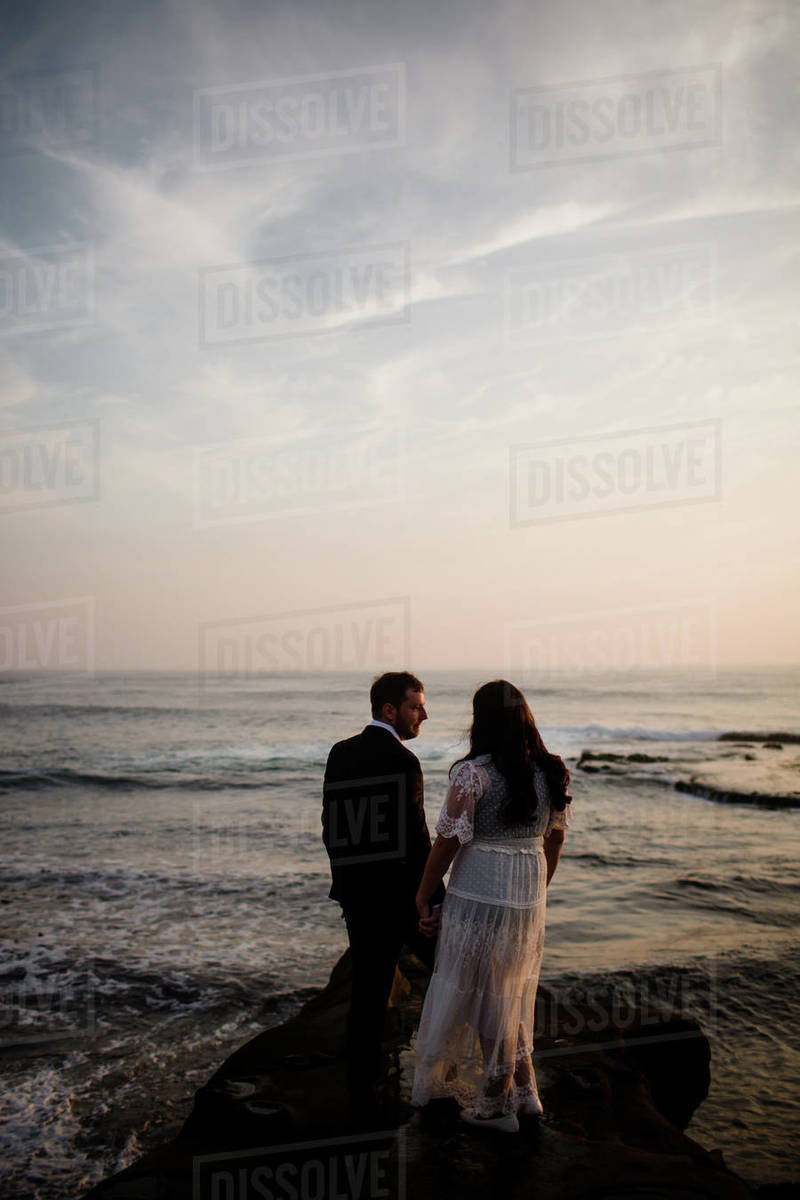 Newlyweds Standing on Rock at Beach in San Diego During Sunset Royalty-free stock photo