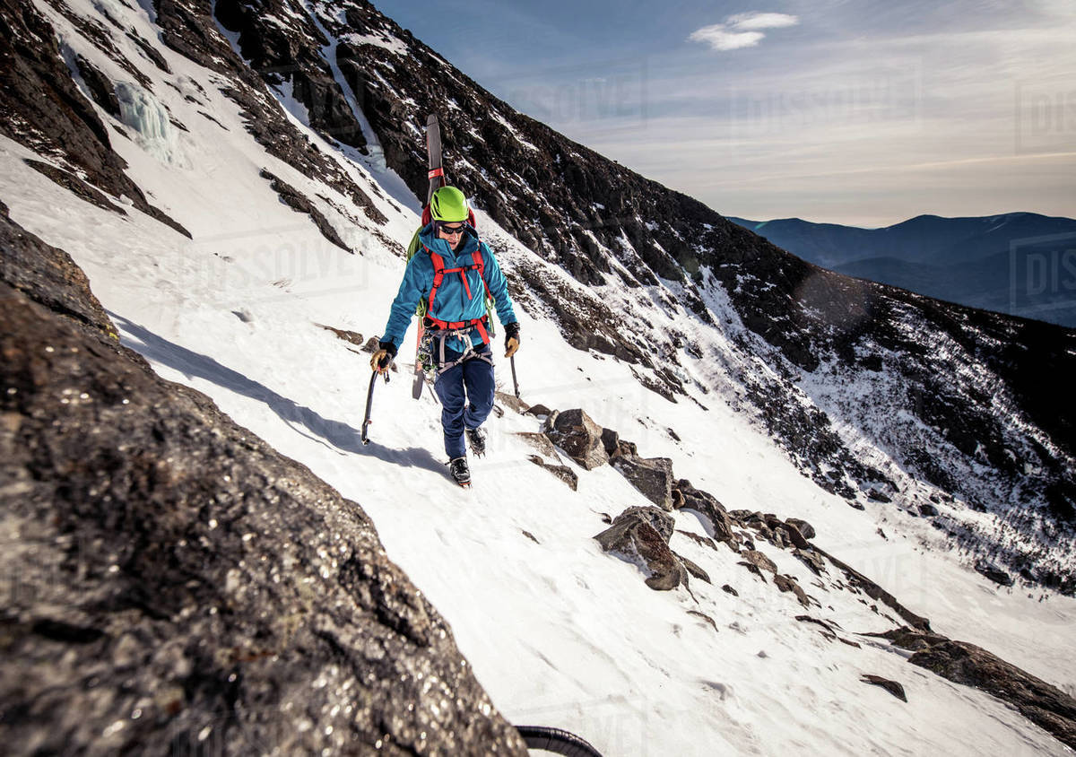 Climber walking through rocks on side of snowy mountain Royalty-free stock photo