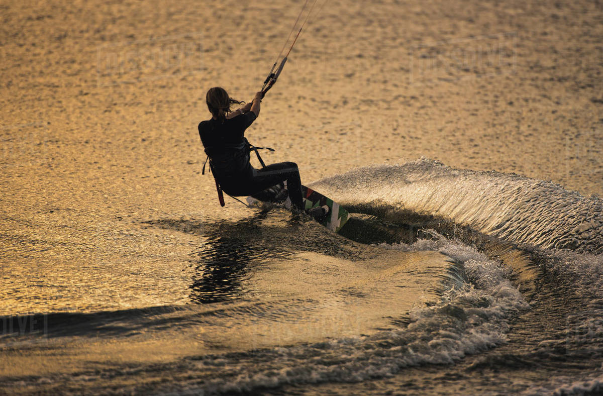 Silhouette of woman kiteboarding with wake Royalty-free stock photo