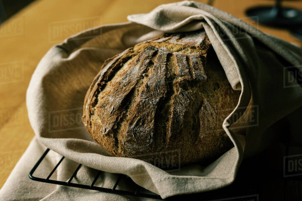 A robust looking fresh artisan sourdough bread loaf on a table Royalty-free stock photo