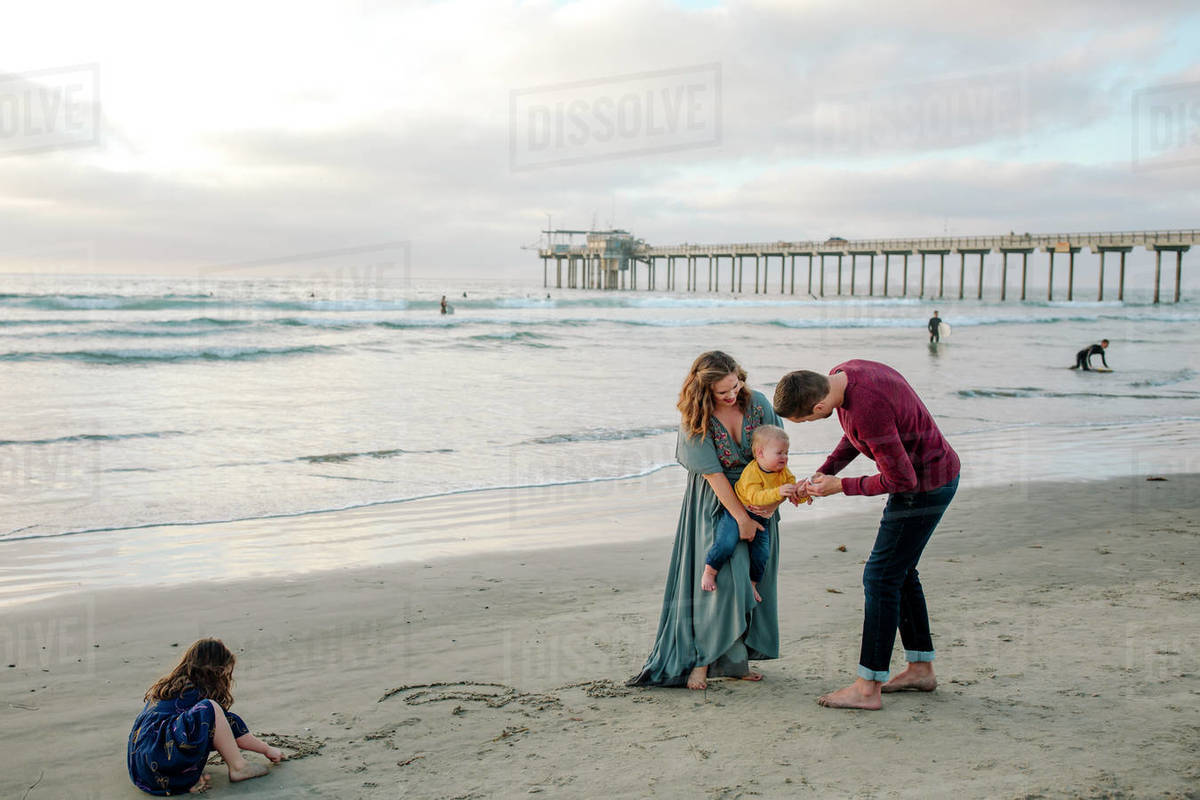 Girl plays in sand as parents check baby brother at beach near pier Royalty-free stock photo