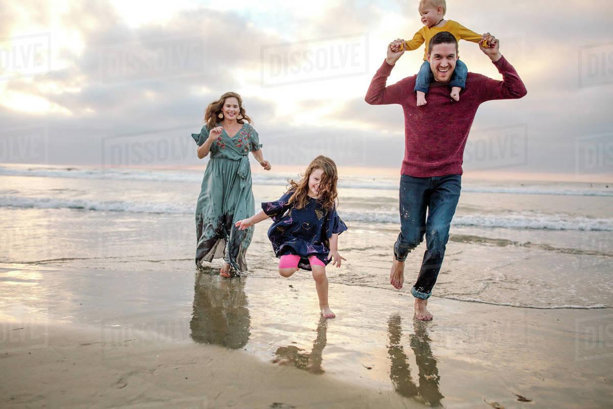 Barefoot laughing family running through ocean surf at sunset Royalty-free stock photo