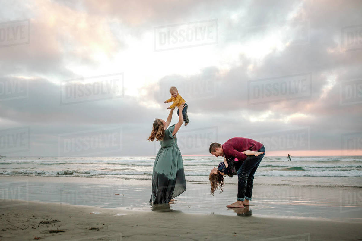 Young parents playing on the beach with children at sunset Royalty-free stock photo