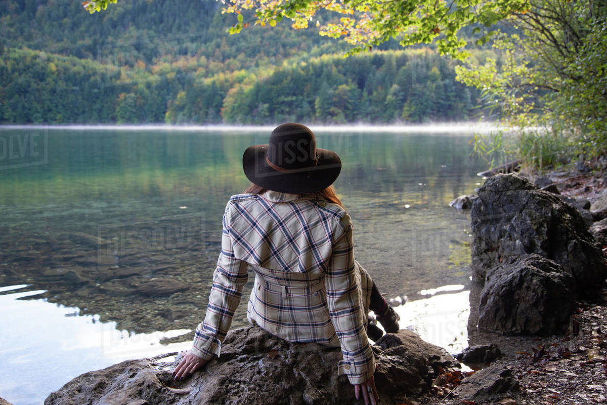 A person sitting and relaxing by an alpine lake Royalty-free stock photo