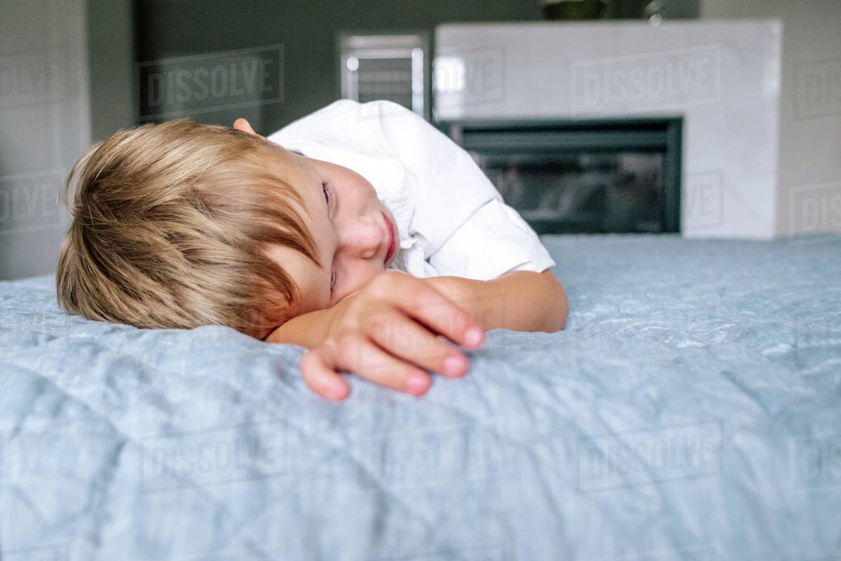 Close up of a young boy laying on parents bed Royalty-free stock photo