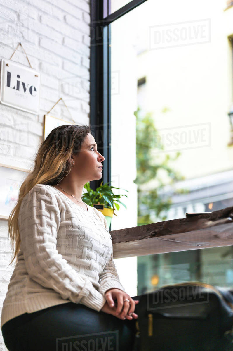 Woman looking up at the window in a coffee shop Royalty-free stock photo