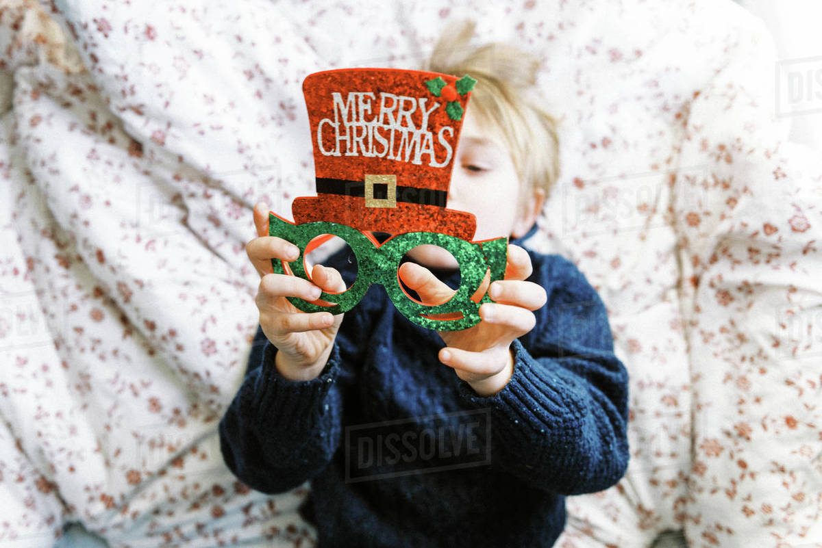 Little boy in a knit sweater looking at Christmas glasses lying on bed Royalty-free stock photo