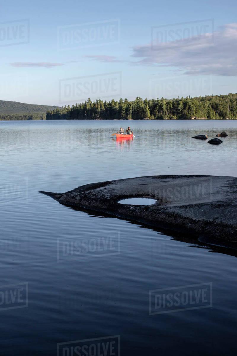 Multi ethnic couple steers canoe towards rocky island on lake in Maine Royalty-free stock photo