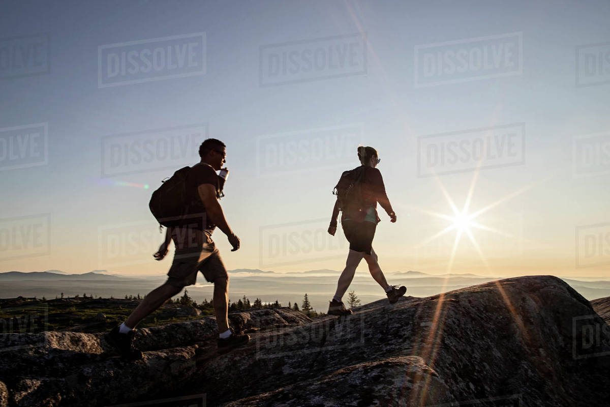 Two hikers reach summit of mountain in Maine at sunrise Royalty-free stock photo